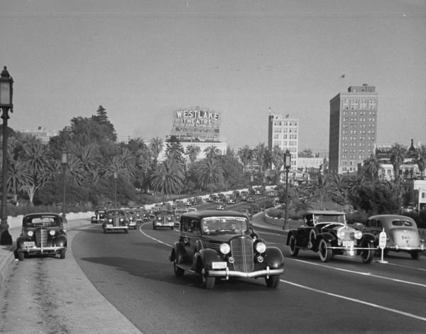 Auto traffic on Wilshire Boulevard during rush hour with sign for the WESTLAKE THEATRE looming in the background --ca. 1938.