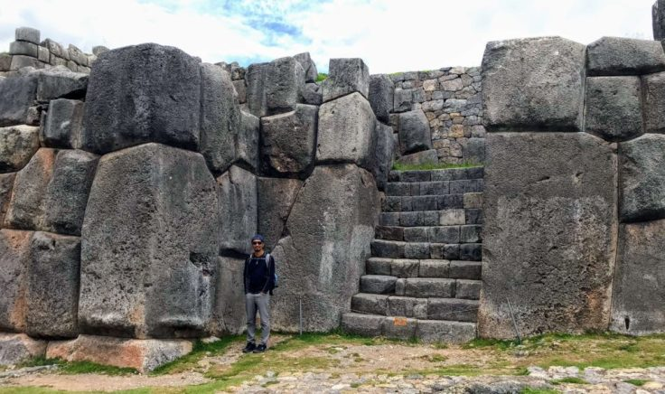 Trin next to massive stones of Sacsayhuaman ancient Inca ruins