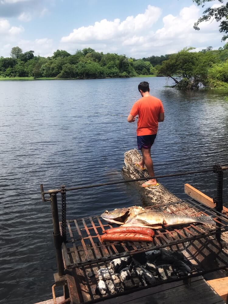 Patrick fishing from one of the logs that the bar is floating on in the Amazon Jungle. Lunch is cooking on the grill.