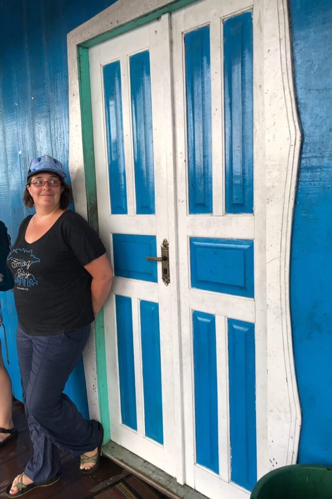 Alia in front of the blue door of the market, a home floating on logs in the Amazon Jungle