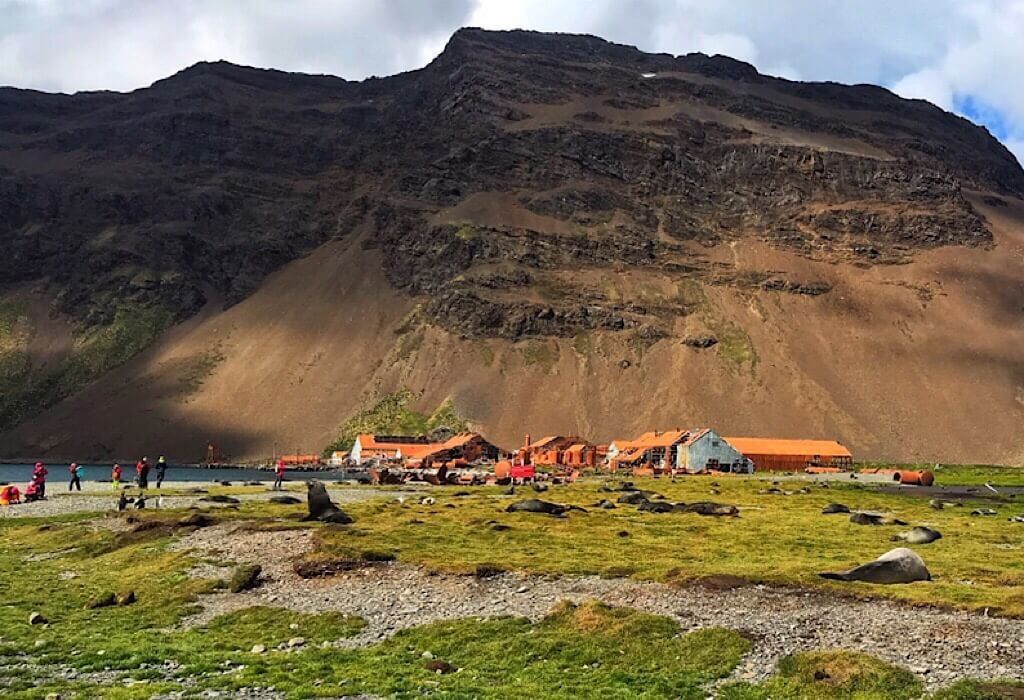 Abandoned whaling station, seals in the foreground, mountain in the background on South Georgia