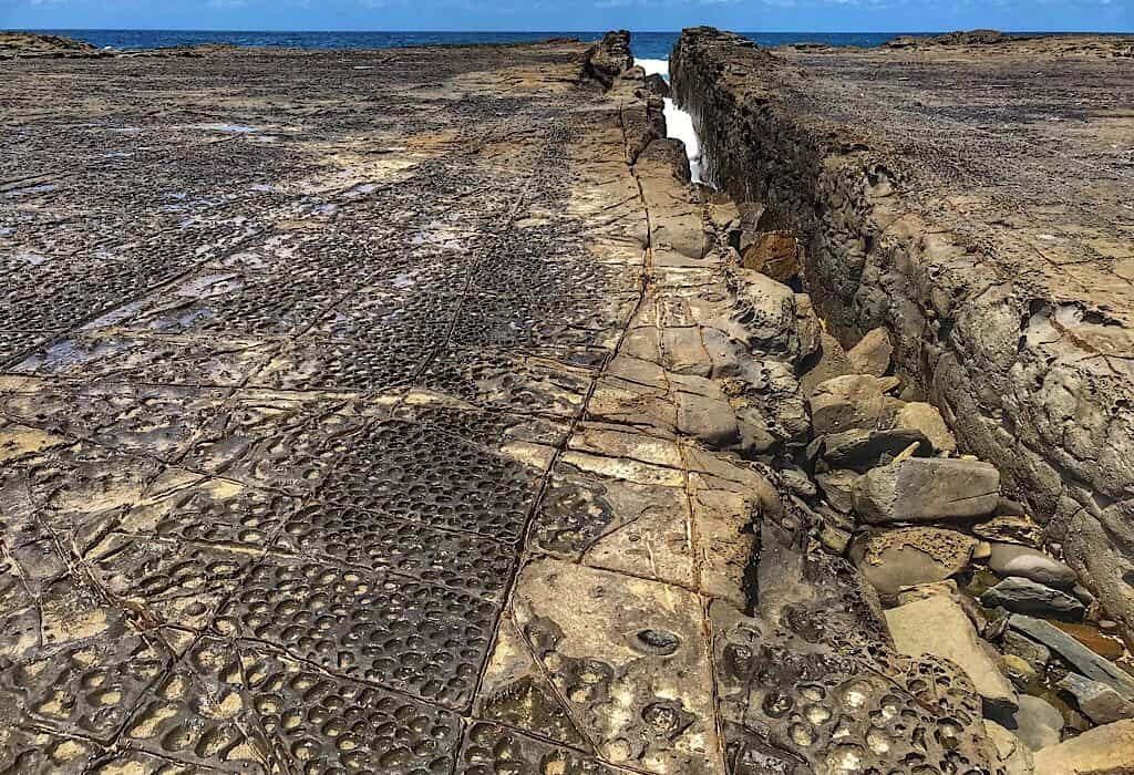 Basalt rock shelf along the coast with a channel of sea water