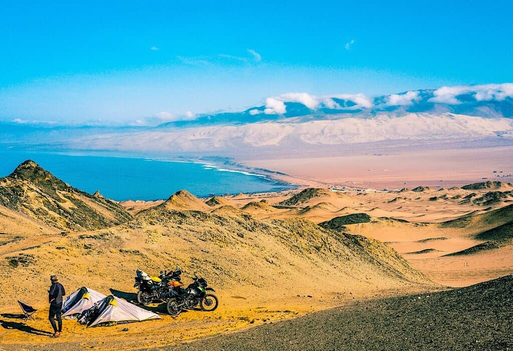 Motorcycles and tents in sand dunes of Peru