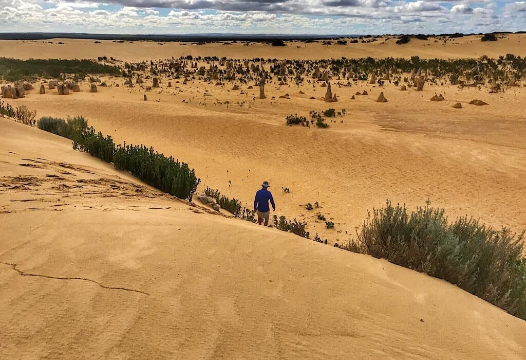 Pinnacles in the distance, Trin walking down a sand dune.