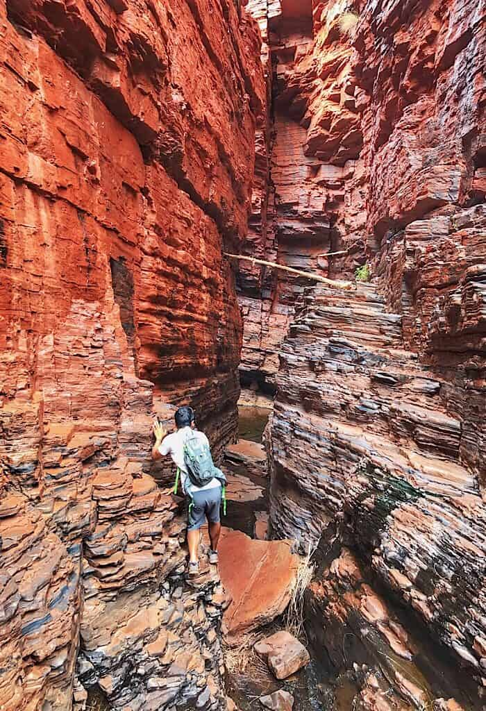 Trin navigation the ledge of a narrow canyon on the way to the Handrail pool in Karijini NP