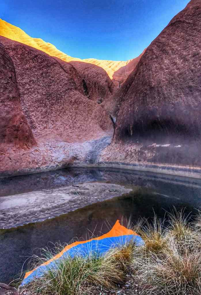 The carved waterway in Uluru to Kapi Matitjulu. Sun making the rocks at the top glow and reflect in the pool below.