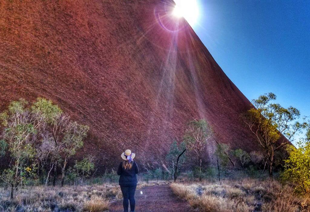 Bonnie approaching Uluru with the sun just peaking out from the side of the mountain