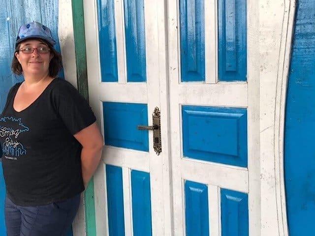 Alia by a blue door in the Amazon Jungle of Brazil