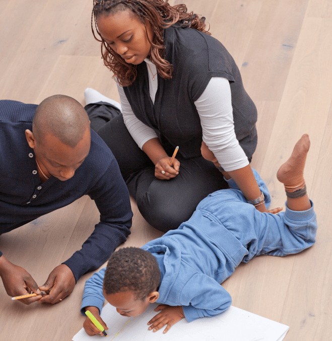Two caregivers, a woman and a man, sit on the floor with a young boy and color with markers
