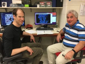 Peter M. Kasson, MD, PhD, (left) and Edward H. Egelman, PhD, with the indestructible virus displayed on screen.