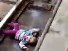 Heart-stopping moment 1-year-old baby fell onto train tracks and a train passed over her but she miraculously survived without a scratch (video)