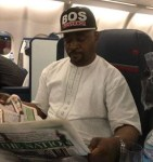 Photos of MC Oluomo On A Plane Heading To The US After Surviving Multiple Stab Wounds At APC Lagos Rally
