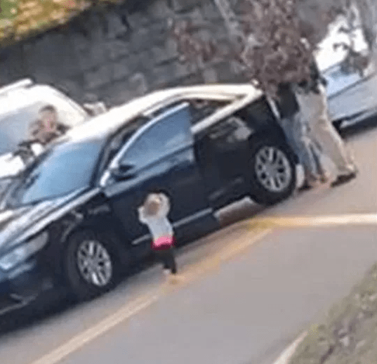 Heartbreaking video shows toddler walking towards armed police with raised hands after her parents were detained