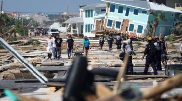 Mexico Beach residents walk down a street on Thursday
