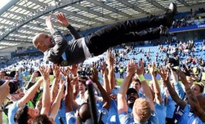 Manchester City boss Pep Guardiola is thrown into the air by his players