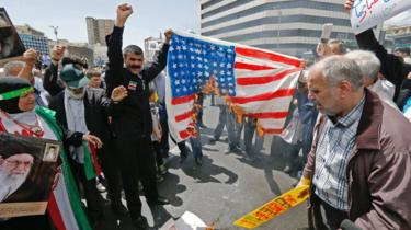 Iranian protesters burn a painted US flag at a rally in Tehran on 10 May 2019