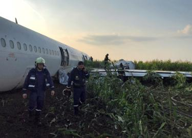 Rescue crews are seen attending to the Ural Airlines Airbus 321 plane after its emergency landing near Zhukovsky International Airport in Moscow Region, Russia.
