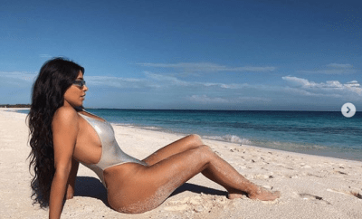 Kim Kardashian poses up a storm in a sexy silver metalic swimsuit (Photos)