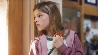 A child holding scissors to protect herself from a shooter