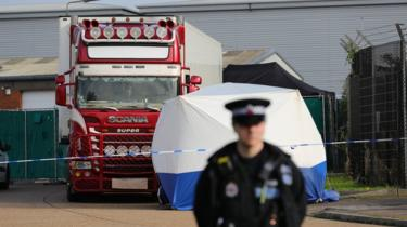 A police officer stands watch in front of the lorry