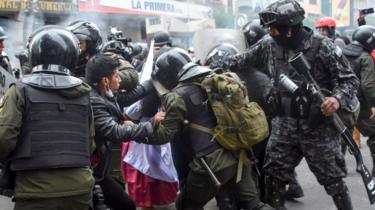 Security forces scuffle with supporters of Bolivian ex-President Evo Morales during a protest in La Paz on 13 November, 2019