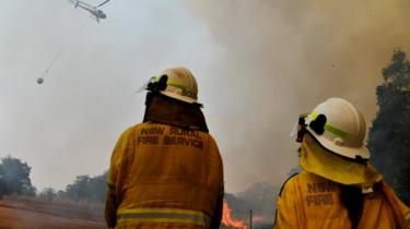Firefighters watch as helicopter surveys a spot fire in Hillside New South Wales on 13 November
