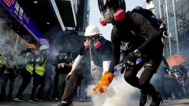 Anti-government protesters in Hong Kong holding a tear gas canister on 20 October 2019