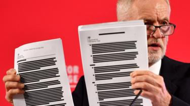 Labour leader Jeremy Corbyn presents redacted documents as he speaks during an election policy announcement on the NHS in London, 27 November 2019