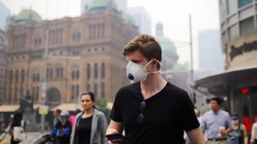 A man wears a face mask to protect himself against the smoke while walking through Sydney's centre on Tuesday