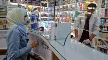 A woman wearing a protective mask shops at a pharmacy in Tehran, Iran (24 February 2020)