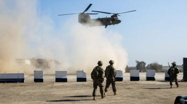 US troops walk as a US Army C-47 Chinook helicopter flies over a village near Mosul
