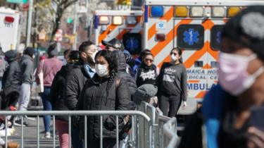 People wait in line to receive a Coronavirus test at Elmhurst Hospital in the Borough of Queens, in New York