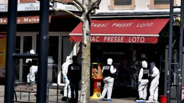 French Police officers wearing protective suits stand in a street in the centre of Romans-sur-Isere, on 4 April 2020