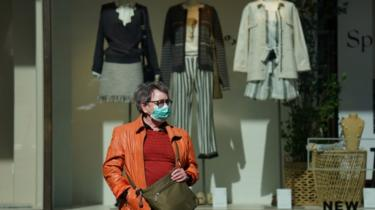 A woman in a face mask outside a clothes shop in Berlin