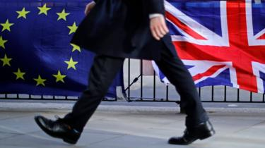 Man walking in front of EU and UK flags