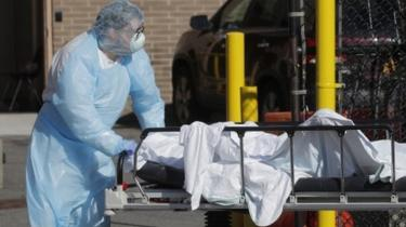 A healthcare worker wheels the body of a deceased person into a makeshift morgue near a hospital in New York. File photo