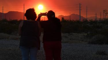 A mother and daughter take photos of the fire