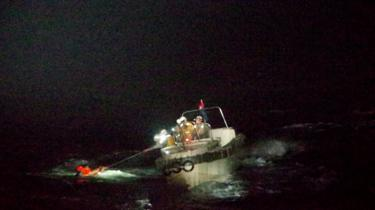 Patrol ship pulling seaman out of the water