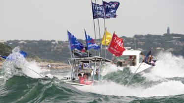 A boat is engulfed in waves from the large wakes of a flotilla of supporters of US President Donald Trump