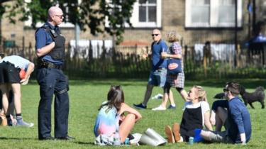 Police speak to people gathering in a park in England