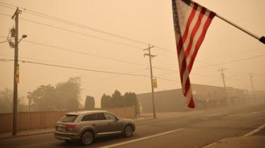 A car and a US flag in the smoke-filled town of Molalla, Oregon