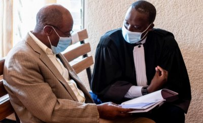 Paul Rusesabagina, portrayed as a hero in a Hollywood movie about Rwanda's 1994 genocide, speaks to his lawyer inside the Kicyikuri Primary Court in Kigali.
