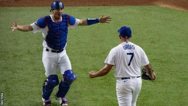 Los Angeles Dodgers relief pitcher Julio Urias and catcher Austin Barnes celebrate beating the Tampa Bay Rays