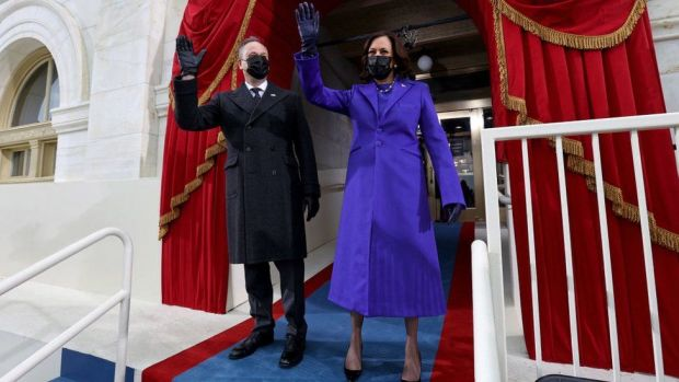 US Vice President Kamala Harris (R) and US Second Gentleman Doug Emhoff wave as they arrive for the inauguration