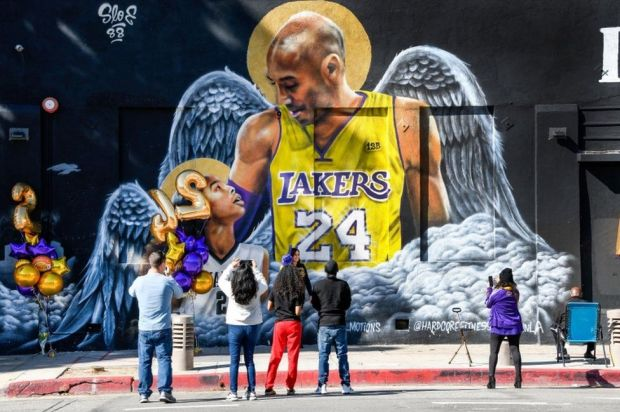 Fans gather at a mural of Kobe Bryant and his daughter Gianna, painted on the wall of Hardcore Fitness Bootcamp gym in downtown Los Angeles.