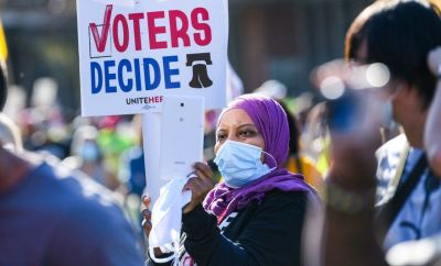 "A protester holds a sign reading ""voters decide"" during an eleciton rally in Philadelphia"