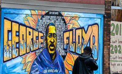 A man walks past the mural of George Floyd