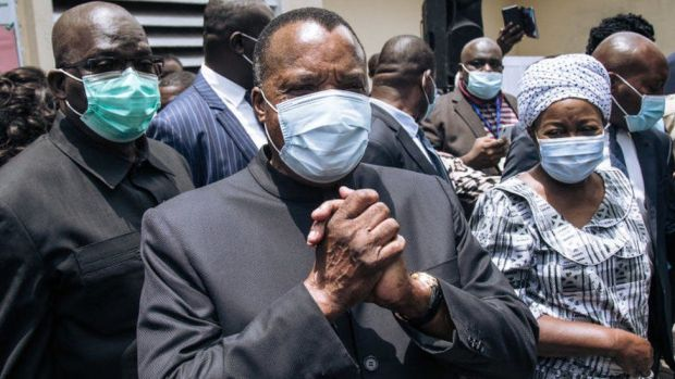 Incumbent Congo President Denis Sassou Nguesso (C) greets officials after casting his ballot in Brazzaville on March 21, 2021.