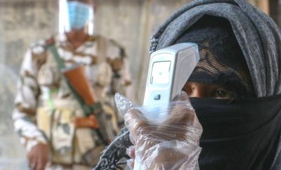 A security personal checks the body temperature of a woman wearing mask shows before her vote at polling station
