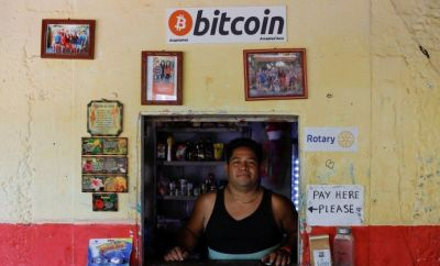 A man standing at his shop which accepts bitcoin as payment